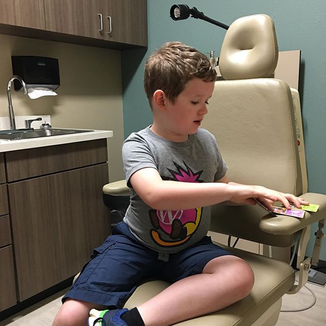 Waiting for his annual hearing test. Always has to have Pokemon cards.